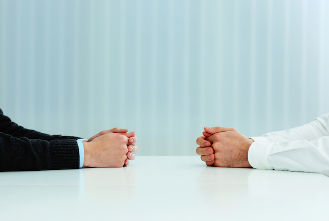 Two businessmen having a discussion. Closeup image of their hands on the table