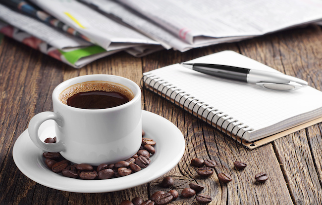 Coffee, newspaper, notepad and pen