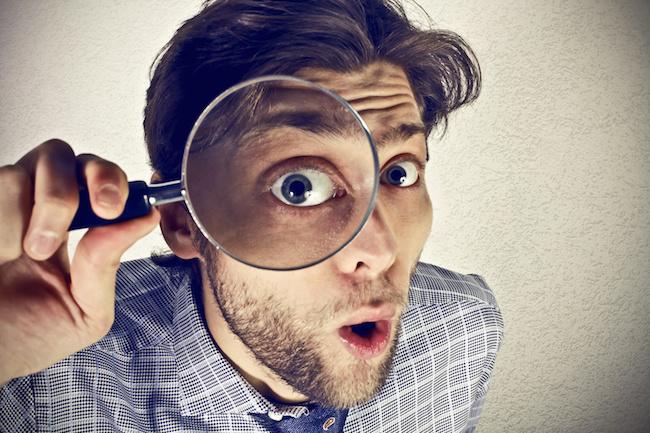 Businessman looks through a magnifying lens