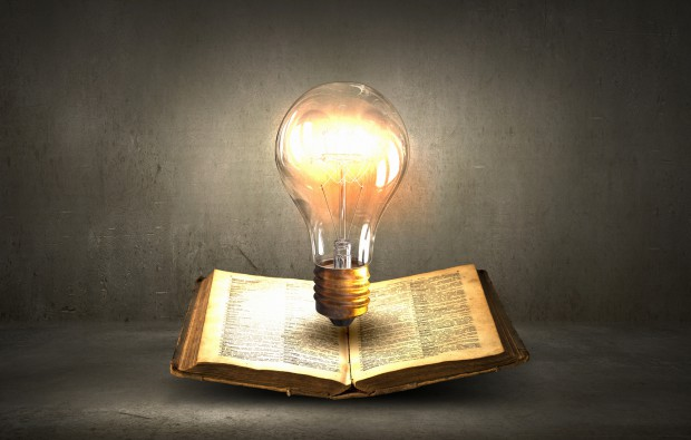 Glass glowing light bulb on opened book