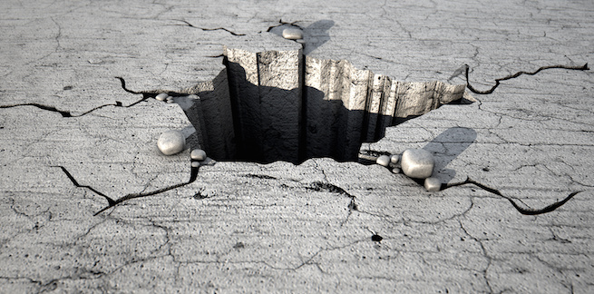 A deep hole cracked out of a flat piece of cracked stone