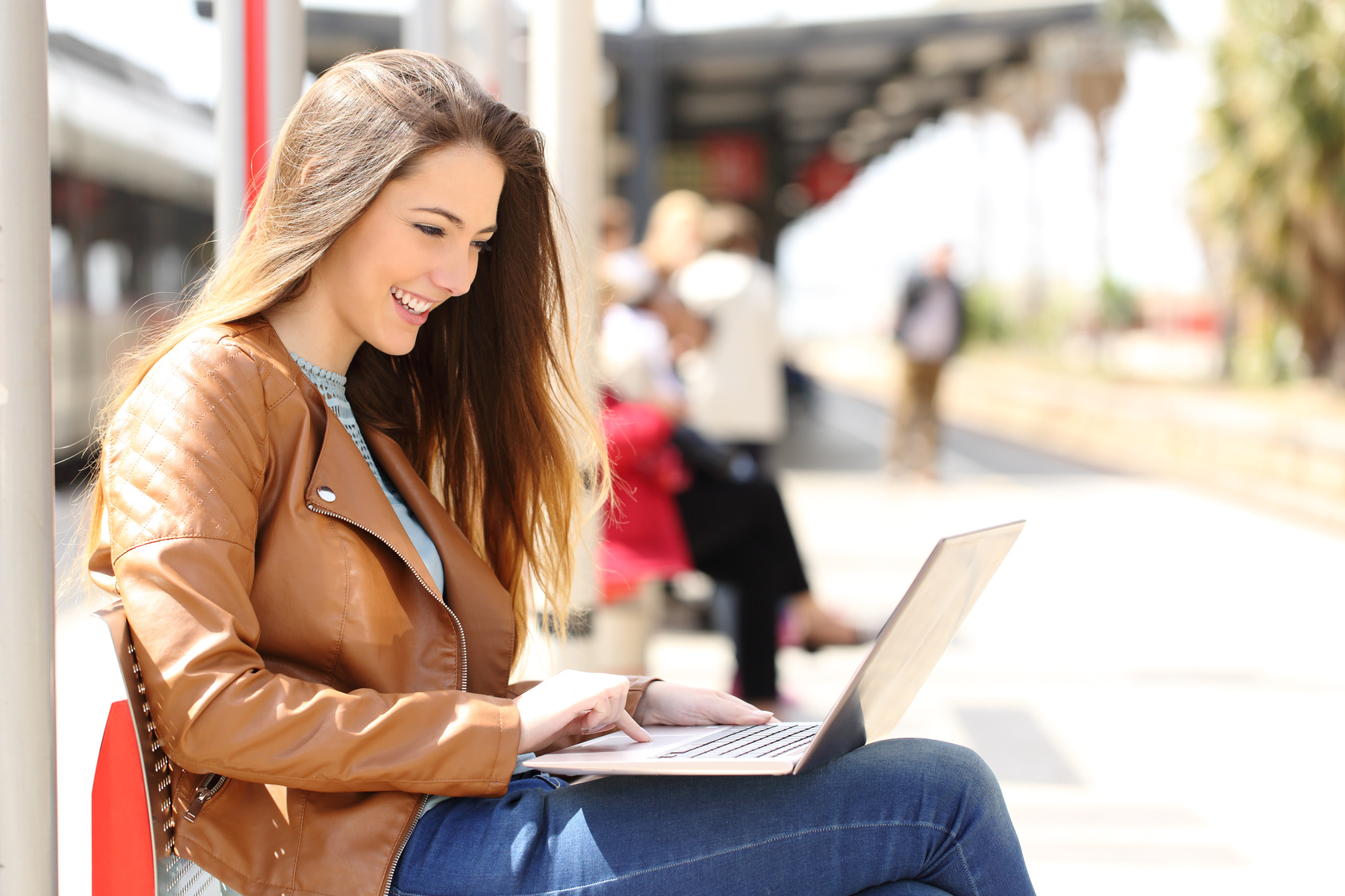 Side view of a girl using a laptop while waiting in a train station in a sunny day