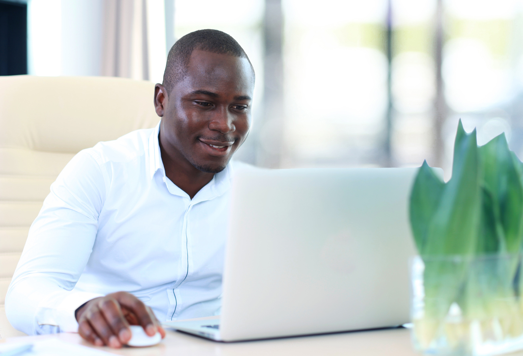 Image of african american businessman working on his laptop.