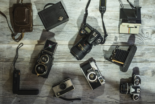 Set of vintage and new cameras on wooden background