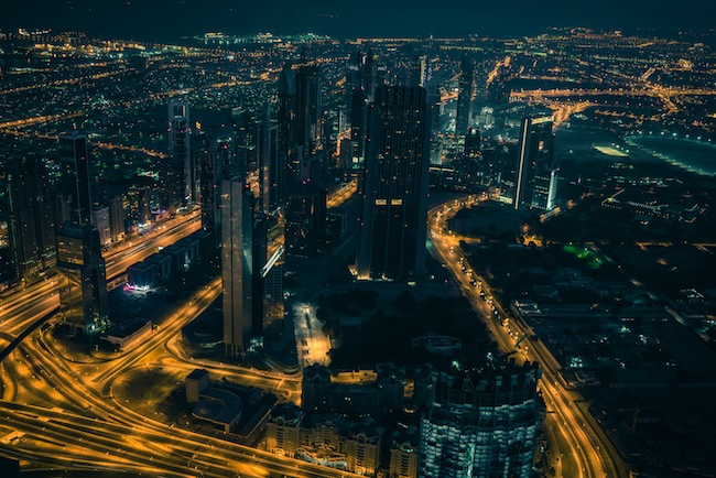 Dubai downtown night scene with city lights. Top view from above
