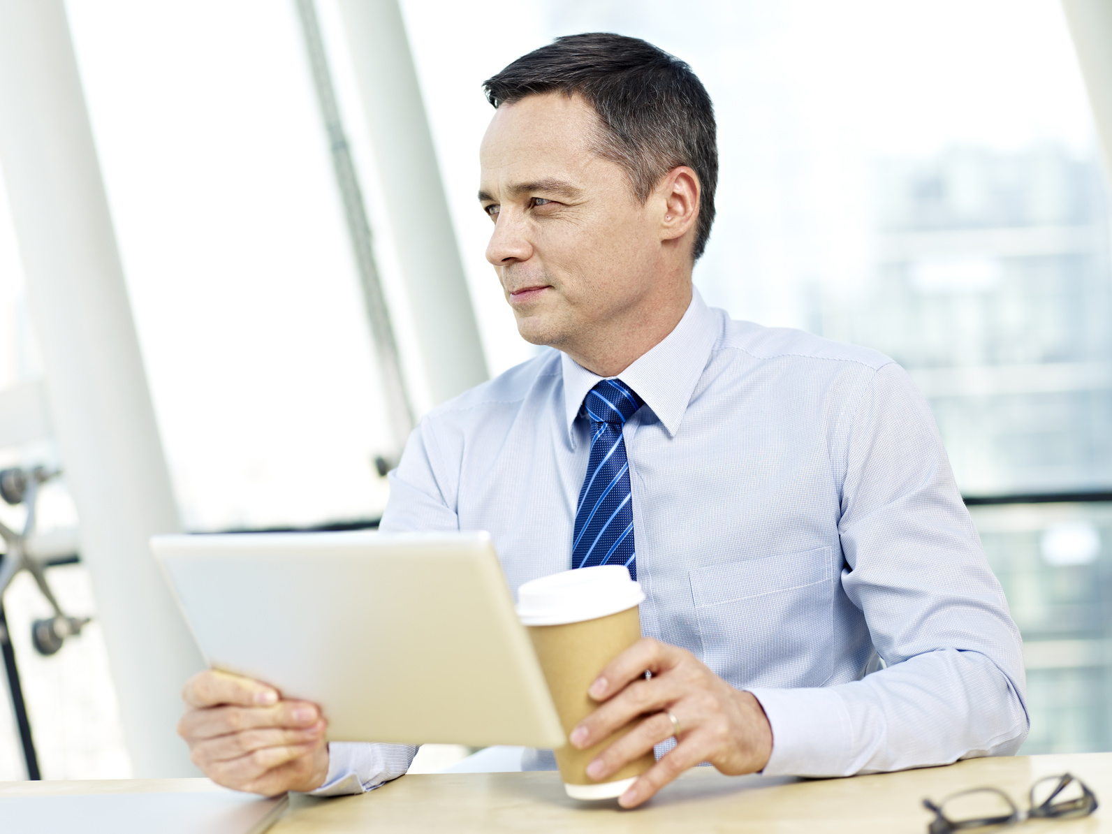 caucasian businessman holding tablet computer and coffee cup looking away thinking in office.