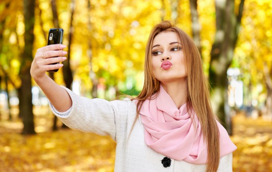 woman taking duckface selfie in autumn city park