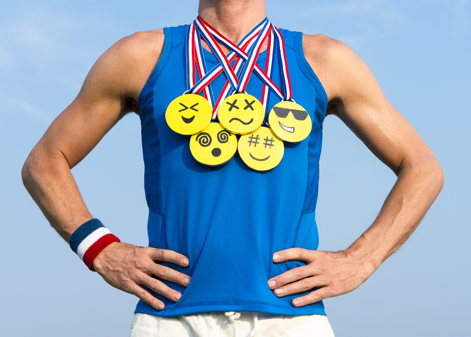 Athlete wearing gold medals with bright yellow emoji faces standing in front of blue sky background