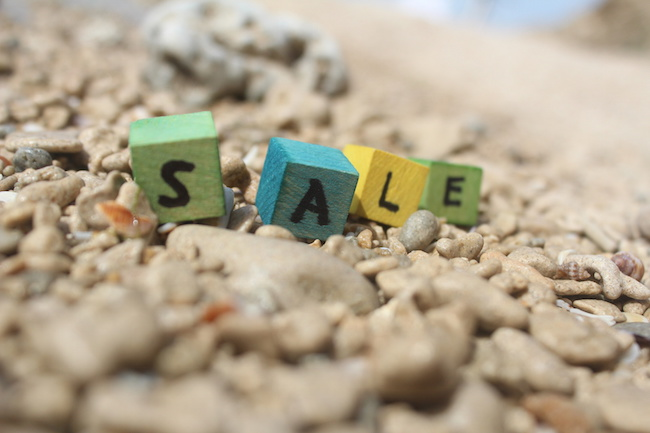 The word SALE written on wooden cubes, at the beach