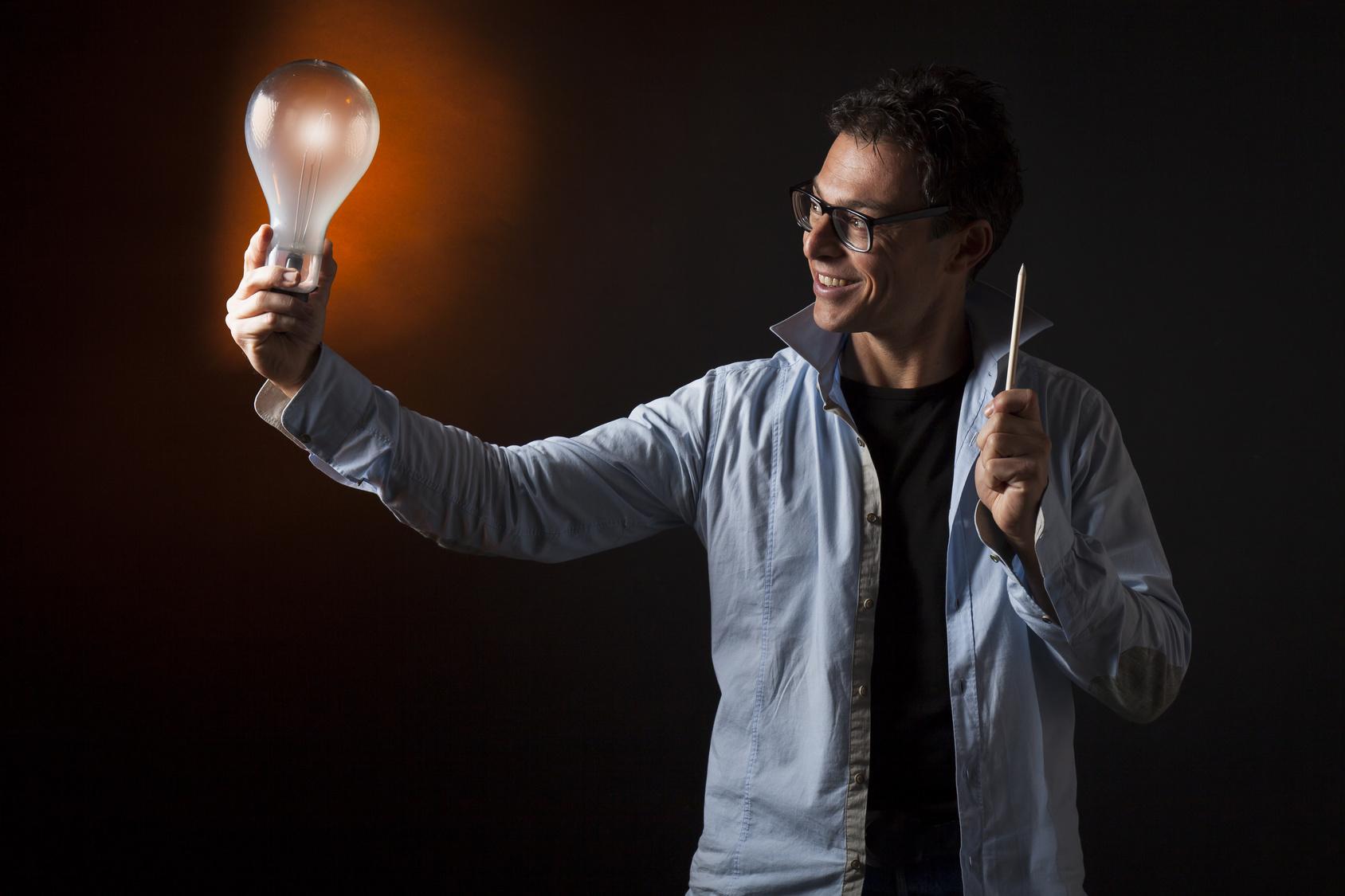 Uomo d'affari tiene in mano una lampadina accesa e nell'altra una matita. Concetto di creativit, genio,  motivazione