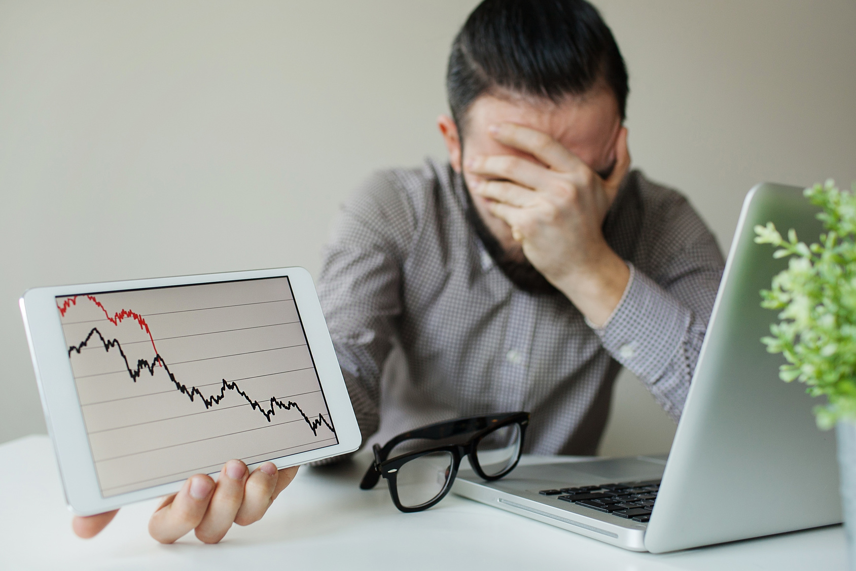 Depressed businessman leaning head below bad stock market chart in office