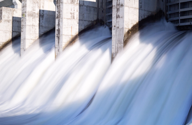 Water rushing out of opened gates of a hydro electric power dam in long exposure