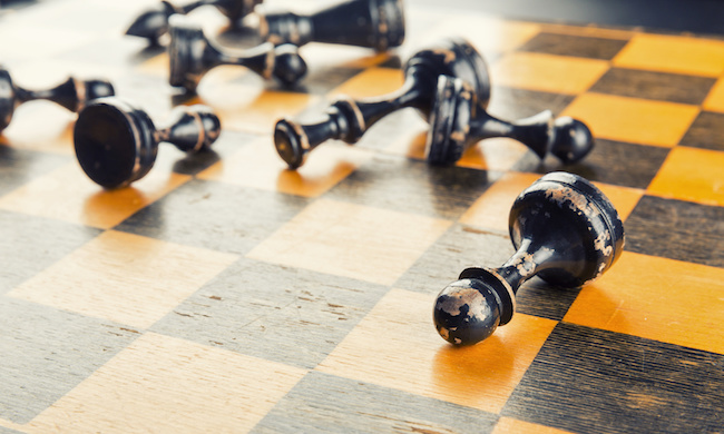 Old wood chess figures lying on the board defeated