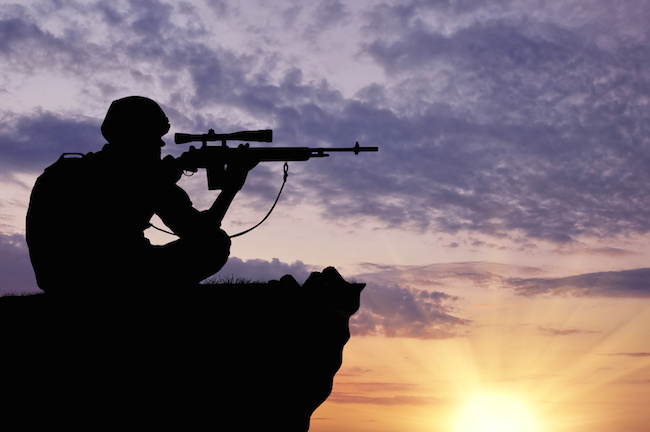 Silhouette of a soldier sniper on top at sunset