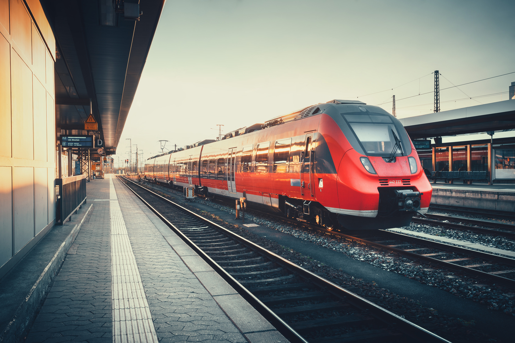 Beautiful railway station with modern red commuter train at colorful sunset in Nuremberg, Germany. Railroad with vintage toning