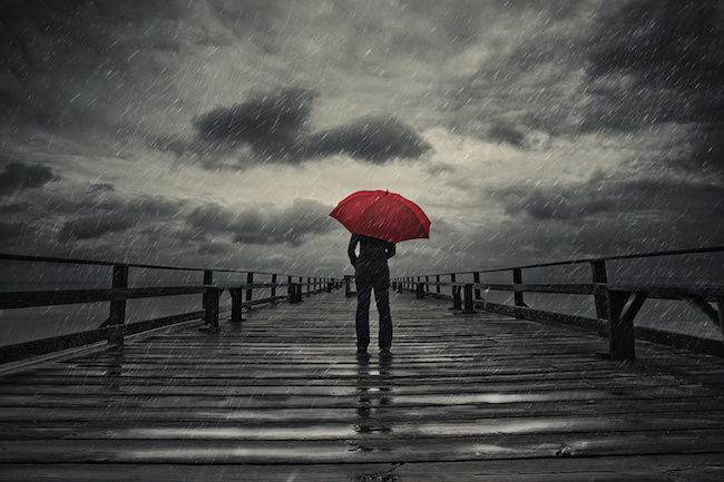 A woman holds a red umbrella on a fishing pier during a storm.