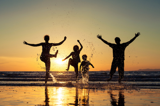 Silhouette of happy family who dancing on the beach at the sunset time. Family having fun on the sea. Concept of friendly family and of summer vacation.