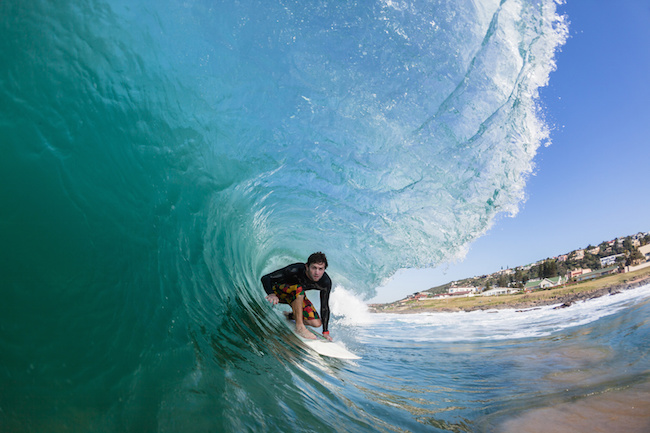 Surfer rides hollow blue ocean wave  tube ride , closeup water photo