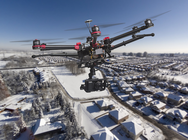 A drone with a camera and raised landing gears flying high above a residential area covered with fresh snow in a bright sunny winter day.