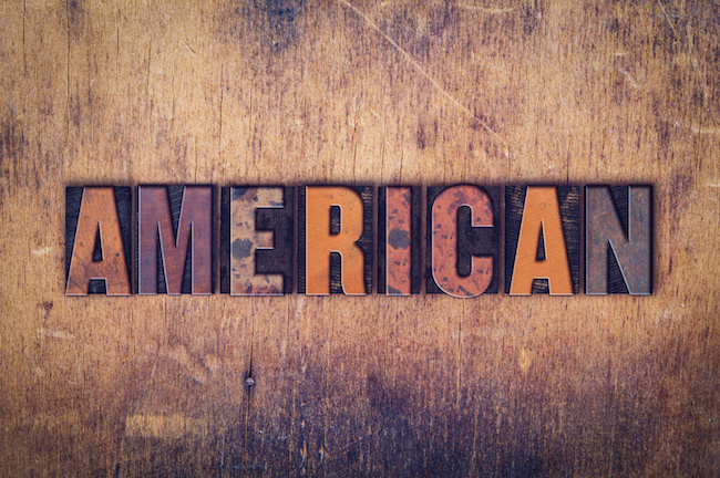 "The word ""American "" written in dirty vintage letterpress type on a aged wooden background."