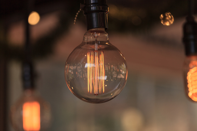 Ornamental light bulb lit up and hanging from the ceiling in a kitchen