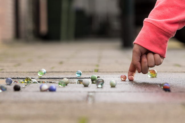 Child playing with marbles on yhe sidewalk.old-fashioned toys still in use today.