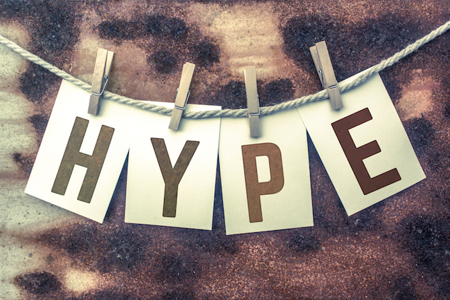 "The word ""HYPE"" stamped on cards and pinned to an old piece of twine over a rusted metal background."