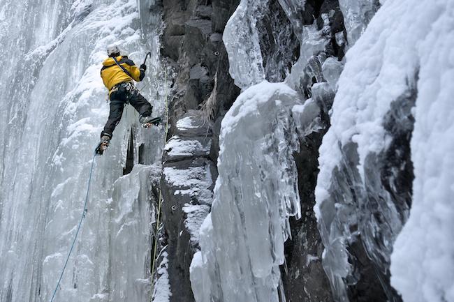 Mann klettert mit Eisgeräten und Steigeisen einen gefrorenen Wasserfall hinauf. Sicherung an Eisschrauben mit Doppelseiltechnik.