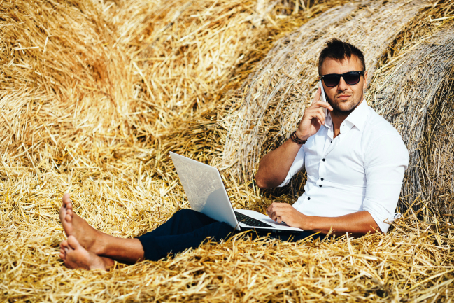 Business man looks beautiful works with a laptop and talking on the phone sitting in a haystack. Summer holidays in the countryside. Work from anywhere. Freelance at work. Series.