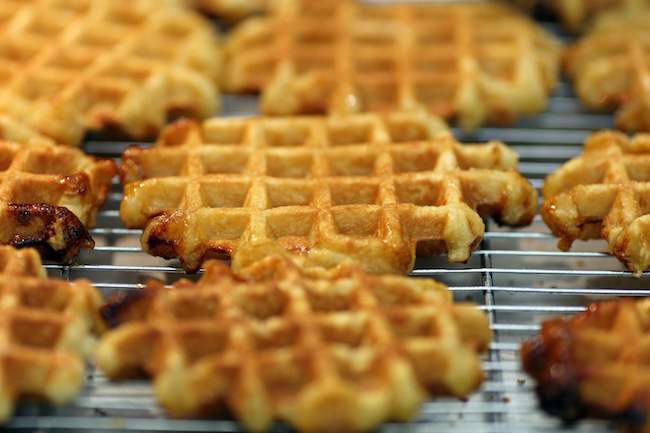 Details of many golden waffles on a grill.